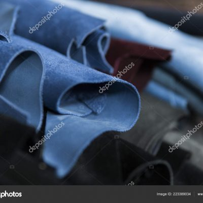 Different pieces of leather in a rolls. The pieces of the colored leathers. Rolls of blue and black leather. Raw materials for manufacture of bags, shoes, clothing and accessories